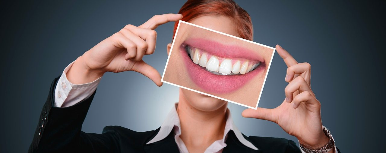 Woman holding up a photo of a bright white smile after flossing correctly
