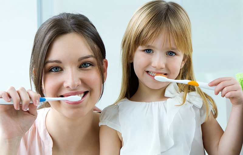 Mother and daughter brushing their teeth before a regular checkup provided by Dentistry at the Grove